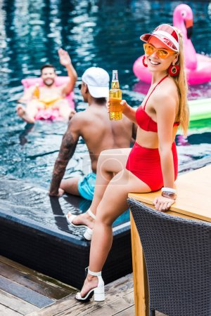 smiling woman sitting with beer while her male friends having fun in swimming pool