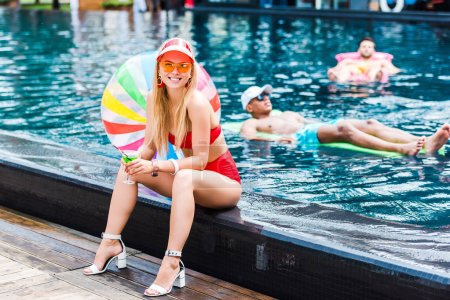 happy young woman in red swimsuit sitting on poolside with cocktail while her male friends resting on inflatable mattresses in pool