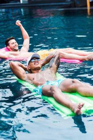 two male friends resting on inflatable mattresses in swimming pool
