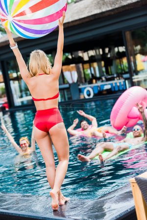 rear view of young woman standing with swimming ball while her friends having fun in swimming pool