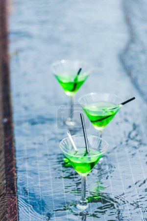 close up view of glasses with green cocktails with straws at poolside