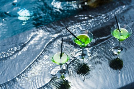 high angle view of glasses with drinking straws in swimming pool