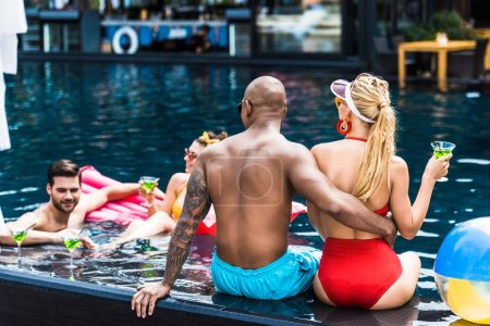 rear view of man embracing girlfriend and talking to friends in swimming pool