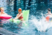 happy young women on inflatable mattresses having fun with swimming ball in pool
