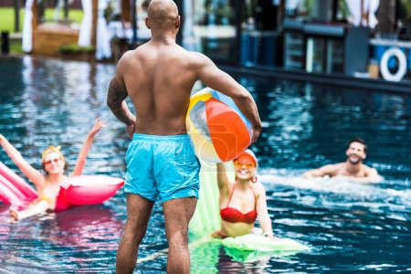 rear view of man standing with swimming ball while his friends in swimming pool with inflatable mattresses