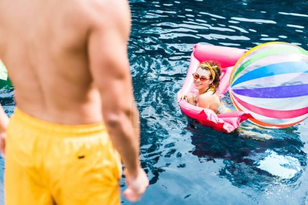 cropped image of man standing on poolside while his girlfriend swimming on inflatable mattress with swimming ball in pool