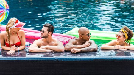 young friends in sunglasses resting in swimming pool near inflatable mattresses