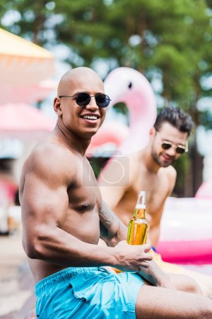 smiling muscular man with beer looking at camera while his friend sitting behind on poolside