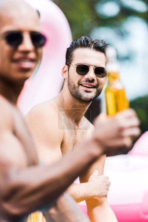 smiling man in sunglasses looking at camera while his friend sitting near with beer