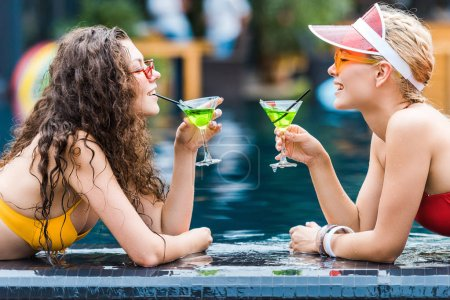 side view of two attractive smiling female friends drinking cocktails on poolside