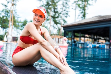 beautiful smiling woman looking away near swimming pool