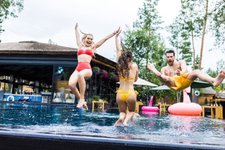 happy friends having fun and jumping into swimming pool