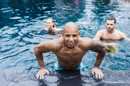 tattooed young man looking at camera while his friends swimming in pool behind