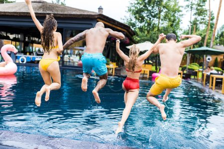 rear view of young friends having fun and jumping into swimming pool