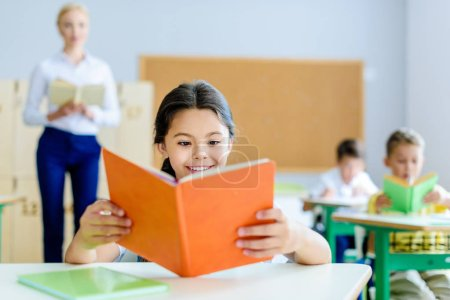 beautiful smiling schoolgirl reading book at classroom during lesson