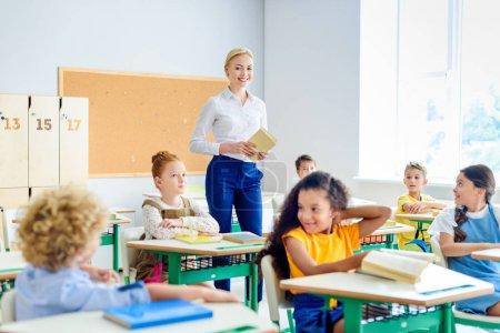 beautiful smiling teacher walking by classroom full of happy children