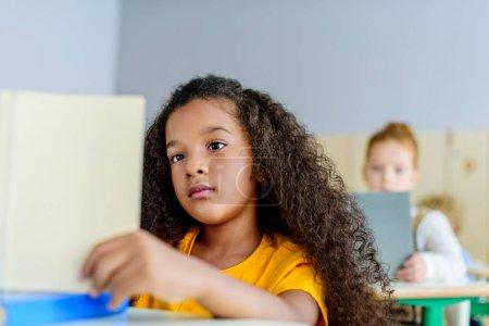 focused little schoolgirl reading book during lesson