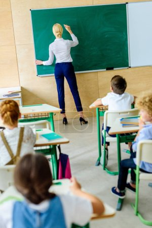 rear view of kids looking at teacher while she writing on chalkboard
