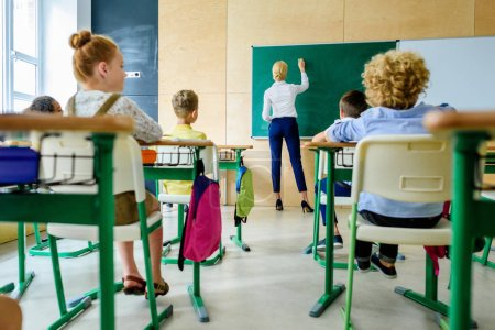 rear view of schoolchildren looking at teacher while she writing on chalkboard