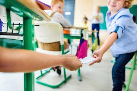 Photo pour Recadrée tir de camarades de classe en passant le message sur papier au cours de la leçon - image libre de droit