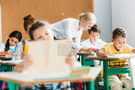 smiling teacher helping children with work during lesson