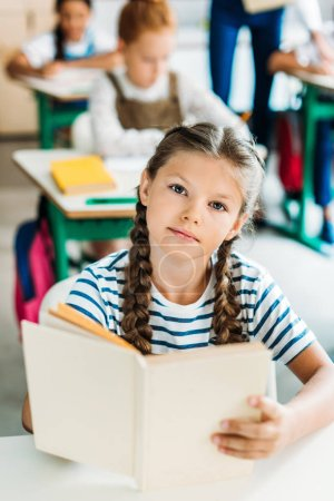 Photo for Beautiful little schoolgirl with book looking at camera during lesson at school - Royalty Free Image