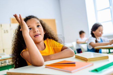 african american schoolgirl raising hand to answer teachers question during lesson