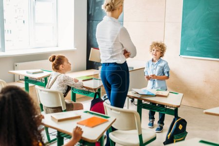 teacher walking by classroom during lesson and talking to little schoolboy