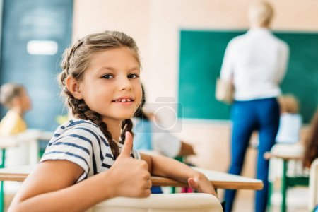 adorable little schoolgirl showing thumb up at camera during lesson