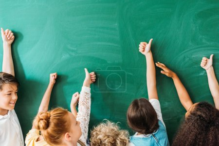 cropped shot of schoolchildren showing thumbs up in front of blank chalkboard