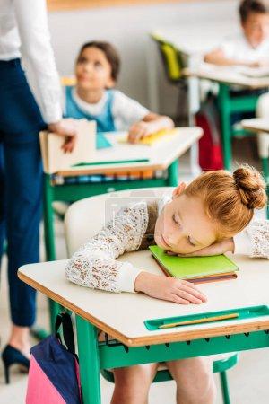 tired little schoolgirl sleeping on desk during lesson