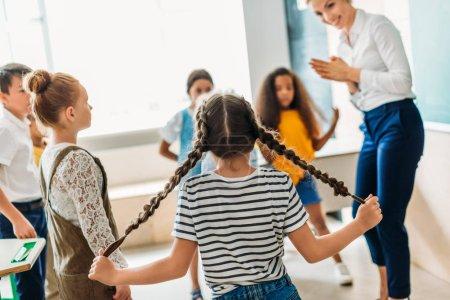 Grupo de compañeros de clase multiétnicas de pie alrededor de profesor en el aula