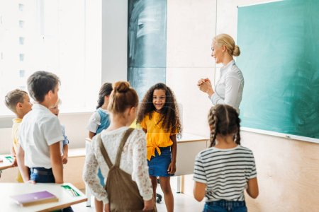 happy multiethnic classmates standing around teacher at classroom