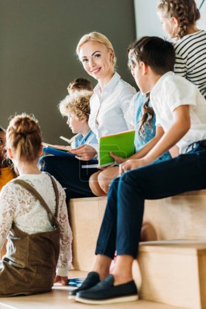 beautiful happy teacher sitting on wooden tribune with schoolchildren at school