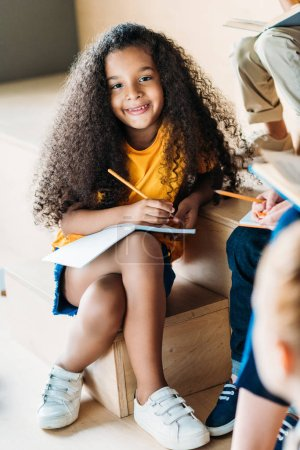 adorable smiling african american schoolgirl writing in notebook and looking at camera