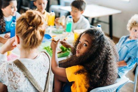 Photo pour Afro-américaine écolière prendre le déjeuner à la cafétéria de l'école avec ses camarades de classe et regarder la caméra - image libre de droit