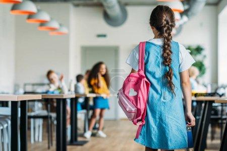 rear view of little schoolgirl in dress walking at school cafeteria