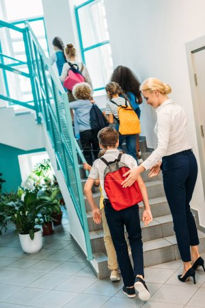 rear view of group of pupils and teacher walking upstairs at school corridor