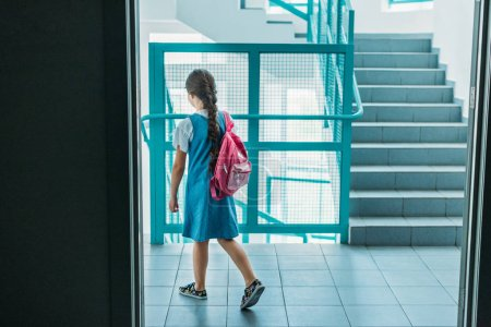 rear view of little schoolgirl in dress walking at school corridor with backpack
