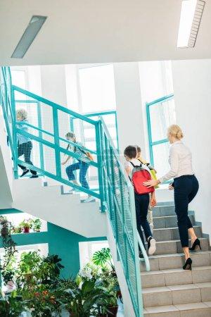 Photo pour Vue arrière du groupe d'écoliers et enseignants marchant à l'étage au couloir de l'école - image libre de droit