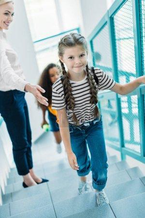Photo pour Vue d'angle élevé d'écolières va à l'étage avec professeur au couloir de l'école - image libre de droit