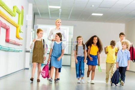 group of happy multiethnic classmates walking by school corridor