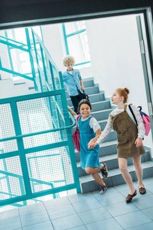 Photo pour Camarades de classe peu heureux en descendant les escaliers à l'école - image libre de droit