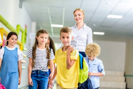 Photo for Group of happy schoolchildren and teacher walking by school corridor - Royalty Free Image