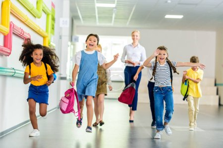 Photo for Adorable happy schoolchildren running by school corridor together with teacher walking behind - Royalty Free Image