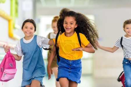 Photo for Adorable happy schoolchildren running by school corridor together - Royalty Free Image