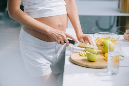 cropped shot of pregnant woman with knife cooking fruits salad at home