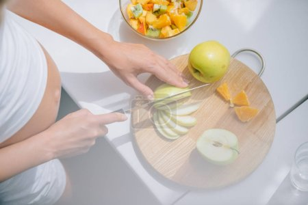 Photo for Cropped shot of pregnant woman with knife cooking fruits salad at home - Royalty Free Image