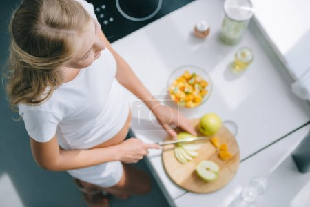 overhead view of pregnant woman with knife cooking fruits salad at home