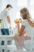 selective focus of pregnant woman eating fruits salad while husband standing at counter in kitchen